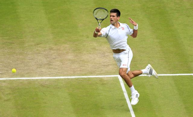 Novak Djokovic of Serbia returns a ball to Roger Federer of Switzerland during the men's singles final at the All England Lawn Tennis Championships in Wimbledon, London, Sunday July 12, 2015. (Jonathan Brady/Pool Photo via AP)
