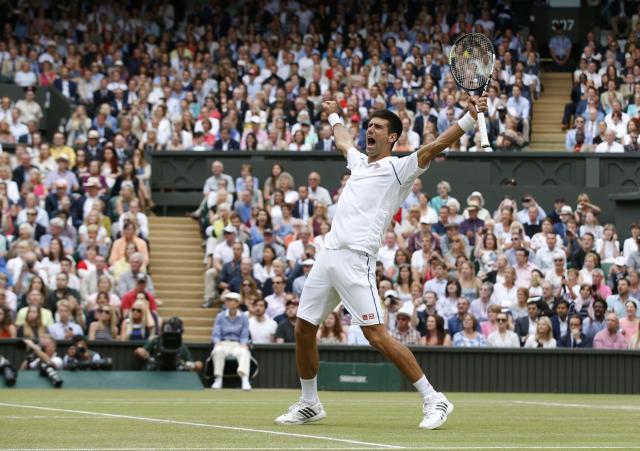 Novak Djokovic of Serbia celebrates winning the men's singles final against Roger Federer of Switzerland at the All England Lawn Tennis Championships in Wimbledon, London, Sunday July 12, 2015. Djokovic won the match 7-6, 6-7, 6-4, 6-3. (AP Photo/Alastair Grant)