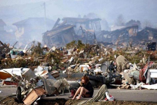 Žena sjedi pored ruševina koje su nastale zbog razarajućeg cunamija, Japan, 2011.