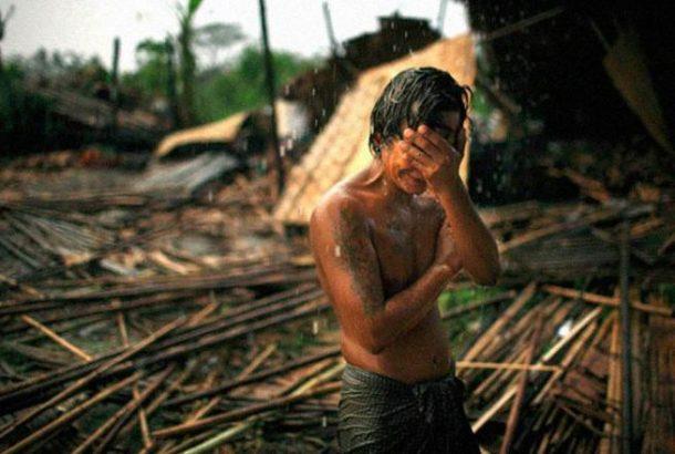 Hhaing The Yu (29) rukama drži svoje lice dok pada snažna kiša kod njegove kuće. Blizina Ranguna. Ovaj ciklon je u maju 2008. godine ostavio milione ljudi kao beskućnike.